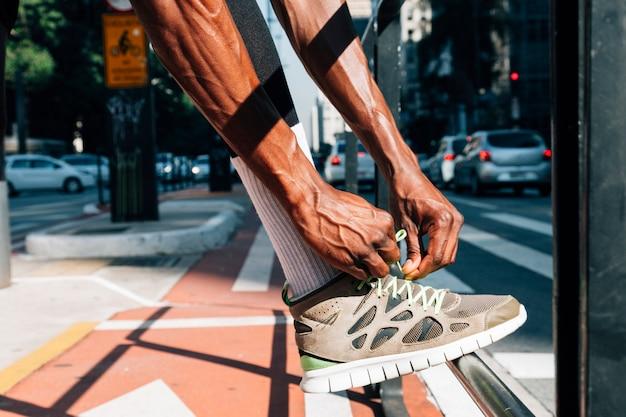 Corridore dell'uomo che lega merletto di scarpe per l'allenamento sportivo su strada Foto Gratuite