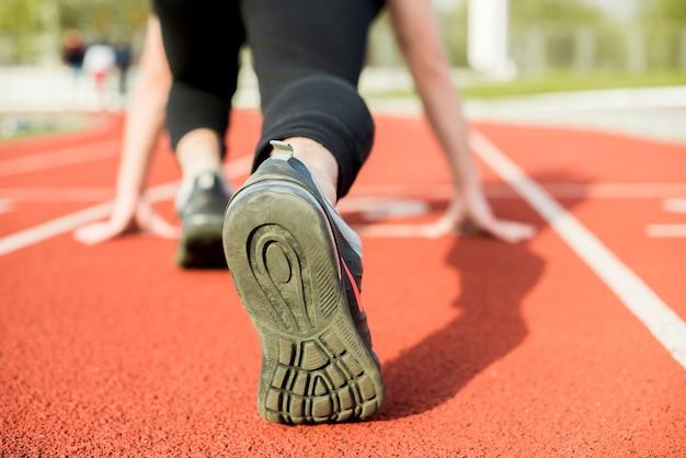 Corridore della giovane donna che si prepara per una corsa in pista Foto Gratuite