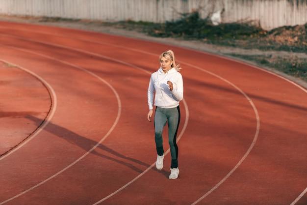 Corridore femminile caucasico in abiti sportivi in esecuzione sullo stadio con le cuffie nelle orecchie. Foto Premium