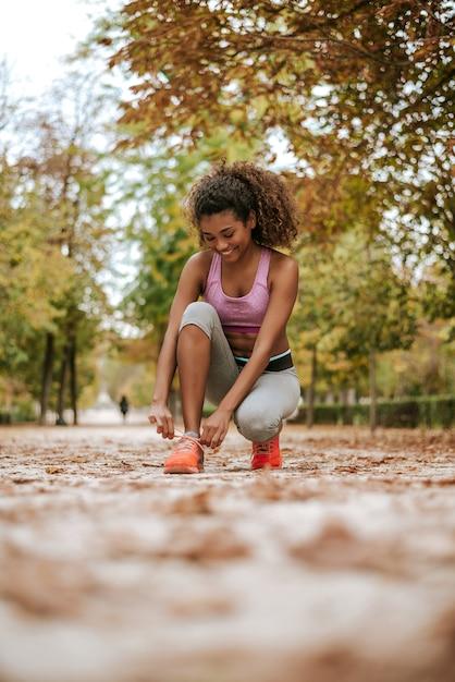 Corridore femminile di forma fisica di sport che si prepara per pareggiare all'aperto nel parco. Foto Premium