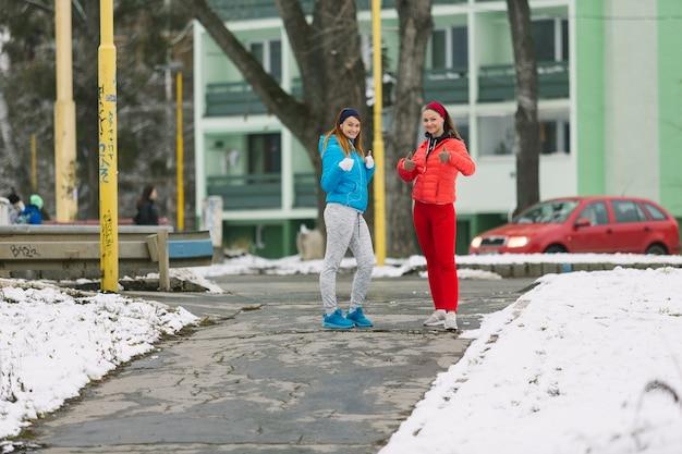 Corridore femminile due che sta sulla via nella stagione invernale che dà pollice sul segno Foto Gratuite