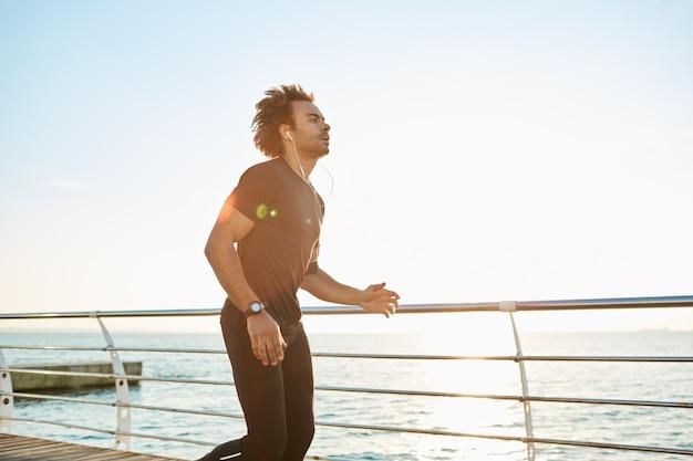 Corridore in abbigliamento sportivo facendo allenamento cardio sulla spiaggia al mattino Foto Gratuite