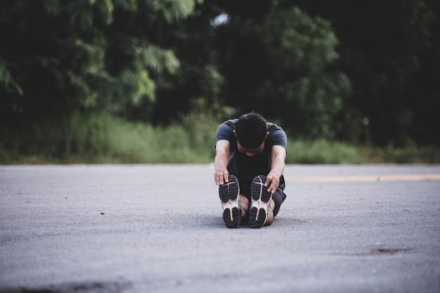 Corridore maschio facendo esercizio di stretching, preparando per allenamento Foto Gratuite
