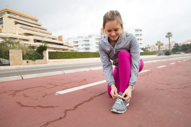 Corridore sorridente che lega merletto della scarpa sportiva sullo stadio Foto Gratuite