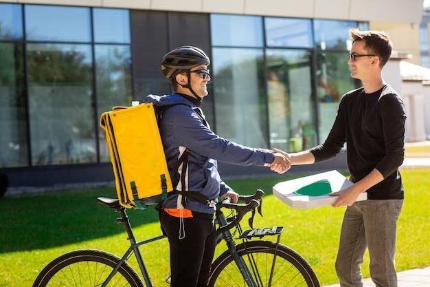 Corriere maschio con bicicletta e borsa termica dando una scatola al cliente sulla strada vicino all'ufficio. Foto Premium