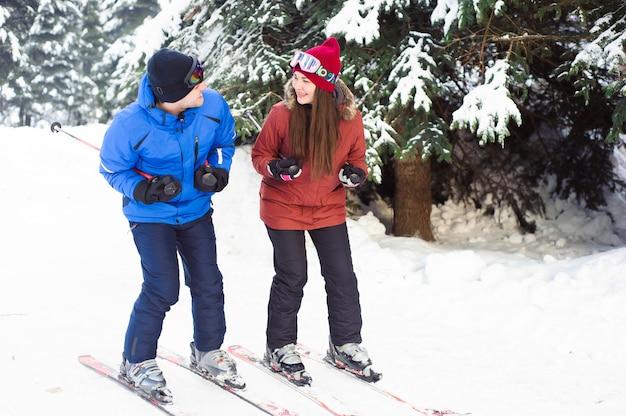 Corsa con gli sci felice della coppia sposata ad una stazione sciistica nella foresta Foto Premium