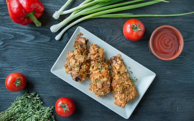 Cosce di pollo fritte croccanti impanate con patatine fritte. le bacchette al forno sono decorate con verdure ed erbe. fast food. cibo sbagliato. sfondo di legno scuro Foto Premium