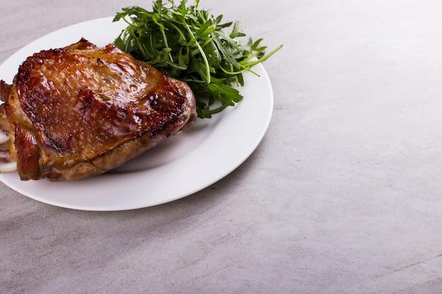 Coscia di tacchino al forno con spezie su un piatto bianco sul ripiano del tavolo. cibo salutare. cena del ringraziamento. Foto Premium