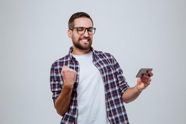 Così felice uomo barbuto in occhiali con lo smartphone Foto Gratuite