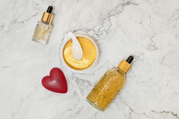 Cosmetici della stazione termale su fondo di marmo. blogger di bellezza. prodotti di bellezza. olio, crema, siero, vaso cosmetico dorato per occhi hydrogel. Foto Premium