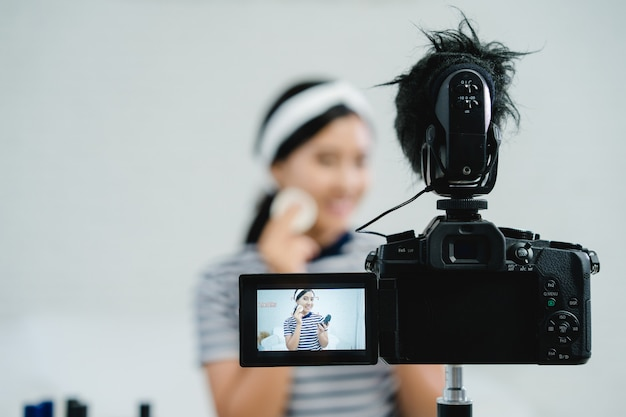 Cosmetici di bellezza del presente di blogger di bellezza mentre sedendosi nella macchina fotografica anteriore per la registrazione del video Foto Gratuite