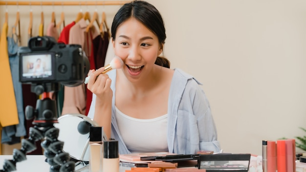Cosmetici di bellezza presenti di bellezza di blogger che si siedono nella macchina fotografica anteriore per registrare video. Foto Gratuite