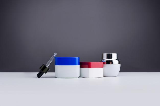 Cosmetici e prodotti di bellezza per la cura del corpo in bottiglie isolate su grigio Foto Premium