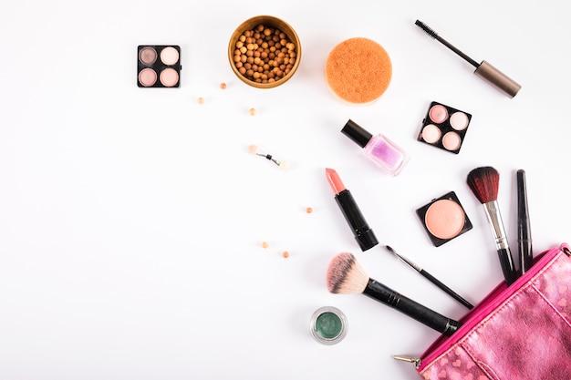 Cosmetici e spazzole di trucco differenti su fondo bianco Foto Gratuite