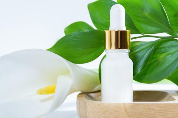 Cosmetici naturali, siero con contagocce, fiore di calla e foglie verdi Foto Premium