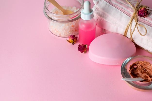 Cosmetici per la cura del viso con scrub organico, maschera, sapone e olio di rosa su sfondo rosa con un asciugamano Foto Premium