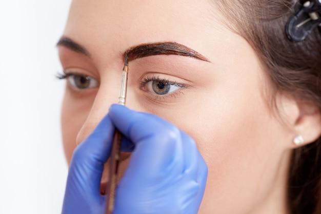 Cosmetologist che applica speciale permanente compongono le sopracciglia. Foto Premium
