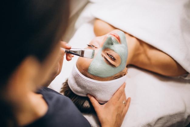 Cosmetologo che applica maschera su una faccia del cliente in un salone di bellezza Foto Gratuite