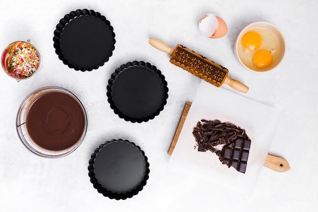 Cospargere; tuorlo d'uovo; mattarello; barretta di cioccolato; sciroppo e tre portarotolo vuoto su sfondo bianco Foto Gratuite