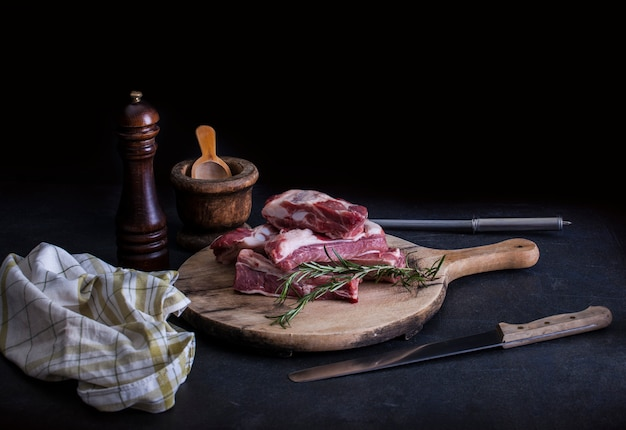 Costine di maiale crude con un rosmarino Foto Premium