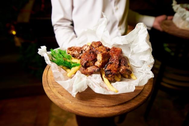Costole fritte con patate ed erbe su un vassoio di legno nella mano del cameriere Foto Premium