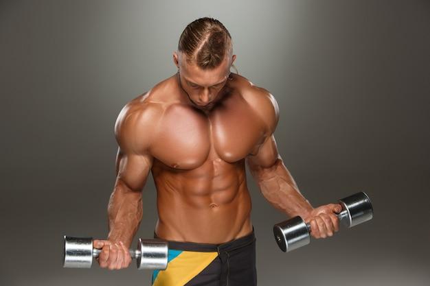 Costruttore di corpo maschio attraente su gray Foto Gratuite