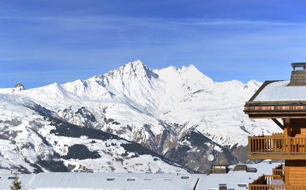 Costruzione del resort di fronte al picco di montagna innevata Foto Premium