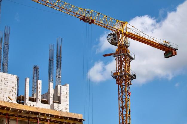 Costruzione di un grattacielo, formazione di supporti in cemento e funzionamento di una gru contro un cielo blu, messa a fuoco selettiva Foto Premium