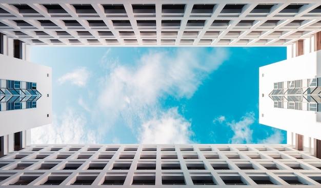 Costruzione moderna di architettura simmetrica con il cielo nuvoloso blu, fondo del grattacielo delle nuvole Foto Premium