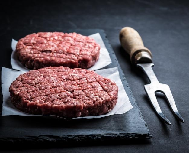 Cotoletta cruda dell'hamburger sulla cottura dell'ardesia Foto Premium