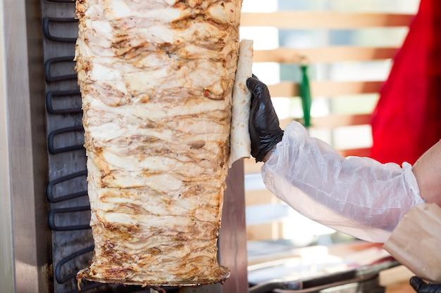 Cottura del kebab turco del doner. lo chef lubrifica il pane pita con il grasso della carne. Foto Premium