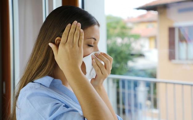 Covid-19 maschera da coronavirus pandemico donna malata starnuti, tosse che soffia il naso Foto Premium