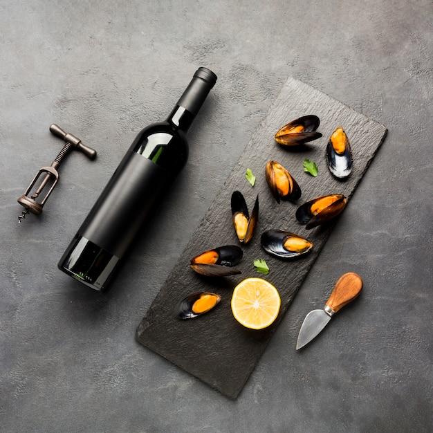 Cozze cotte e bottiglia di vino piatte Foto Gratuite