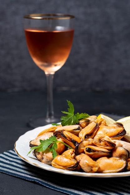 Cozze del primo piano con un bicchiere di vino Foto Gratuite