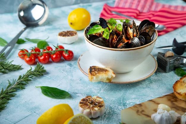 Cozze in piastra servito con pomodori, toast e limone e aglio Foto Premium