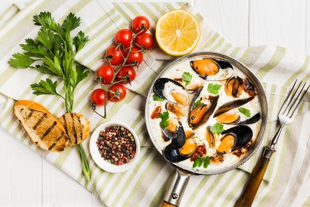 Cozze piatte in salsa bianca e lati sulla tovaglia Foto Gratuite