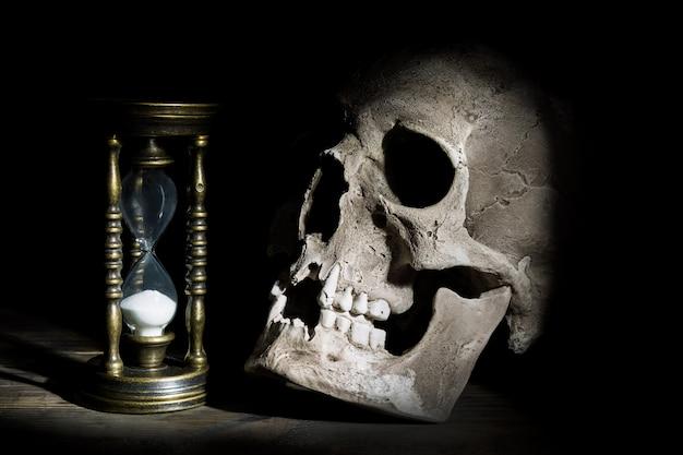 Cranio e clessidra vintage su sotto il fascio di luce in legno Foto Premium