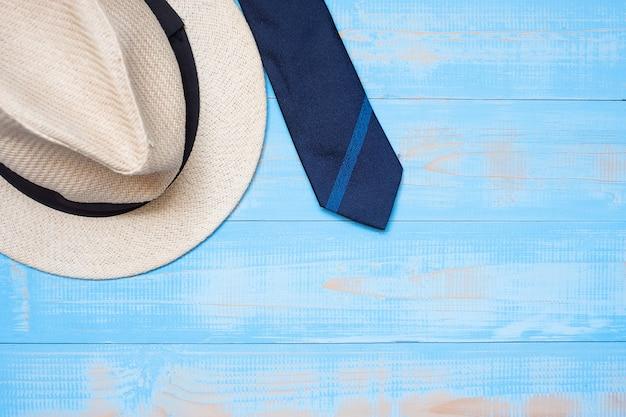 Cravatta blu con il cappello su fondo di legno con lo spazio della copia per testo Foto Premium
