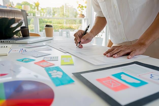 Creative web designer pianifica l'applicazione e sviluppa il layout del modello, framework per telefono cellulare. concetto di esperienza utente (ux). Foto Premium
