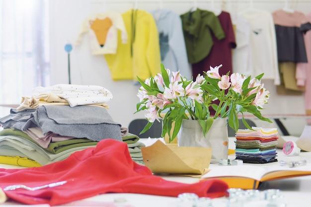 Creativo designer di moda scrivania o sul posto di lavoro con attrezzature da cucire, tessuti, modelli, stilista moderno ufficio di ispirazione, atelier di sarta con vestiti Foto Premium