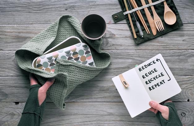 Creativo piatto disteso, zero sprechi pranzo con set di posate in legno riutilizzabili, scatola per il pranzo in panno di cotone e tazza di caffè riutilizzabile. stile di vita sostenibile, testo