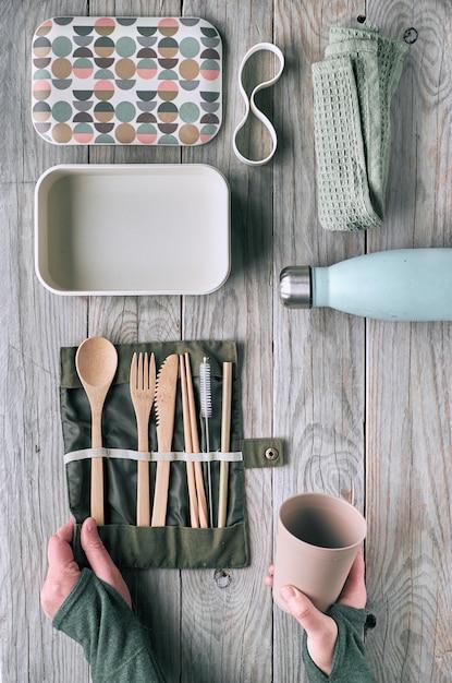 Creativo piatto lay, zero spreco concetto di pranzo con set di posate in legno riutilizzabili, scatola per il pranzo, bottiglia per bere e tazza di caffè riutilizzabile. vista dall'alto stile di vita sostenibile, layout piatto su legno invecchiato. Foto Premium