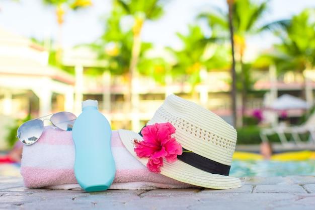 Crema solare, cappello, occhiali da sole, fiori e torre vicino alla piscina Foto Premium