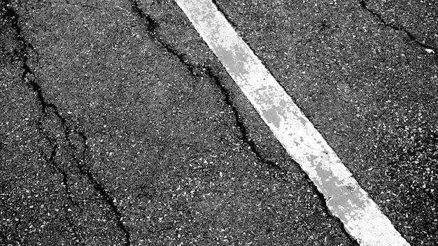 Crepa e struttura della strada asfaltata con la linea tratteggiata bianca fondo di vista superiore. Foto Premium