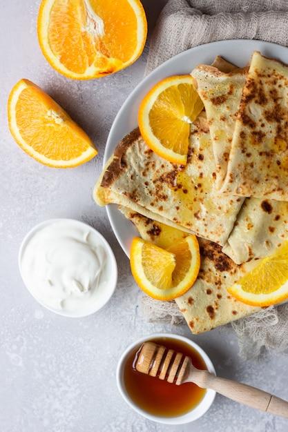 Crepes con arancia, miele e yogurt naturale o panna acida. pancakes sottili. Foto Premium