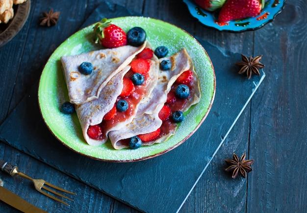 Crepes fatte in casa fresche servite su un piatto con fragole e mirtilli su un fondo di legno scuro Foto Premium