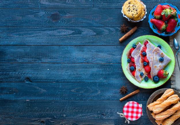 Crepes fresche fatte in casa servite su un piatto con fragole e mirtilli, su uno sfondo di legno scuro, Foto Premium