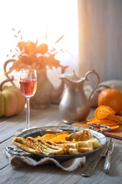 Crepes suzette su piastra metallica vintage sul tavolo di legno servito con salsa all'arancia Foto Premium