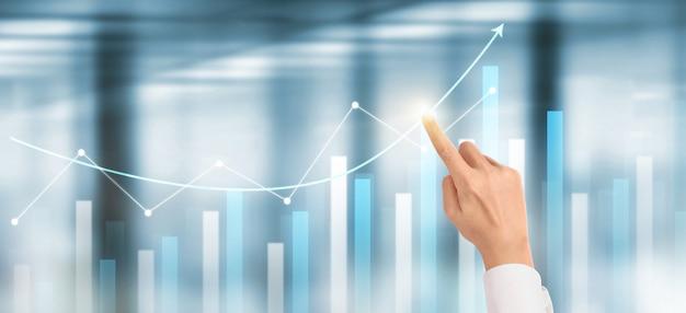 Crescita del grafico del piano dell'uomo d'affari della mano e aumento degli indicatori positivi del grafico nel suo affare Foto Premium