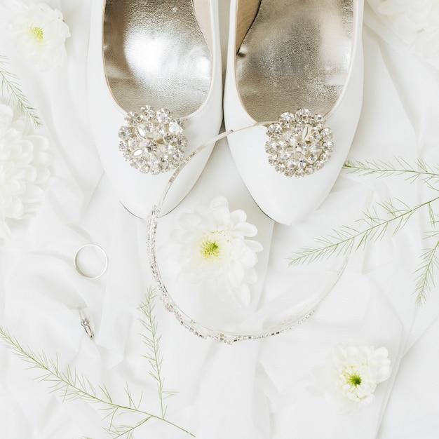 Crisantemo; fedi nuziali; corona vicino alle scarpe da sposa sulla sciarpa Foto Gratuite